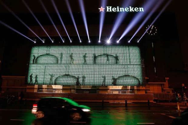 AMSTERDAM, NETHERLANDS - DECEMBER 07: A general view of the Heineken Light Installation at Heineken Experience on December 7, 2012 in Amsterdam, Netherlands. Heineken marks its 140-year anniversary by inviting people to be part of the celebration in a major light installation on the wall of its spiritual home, brought to life through social media. Created from 5,000 iconic Heineken bottles the LED-lit exhibit will stand tall outside the Heineken Experience in the centre of Amsterdam, December 7th 2012- January 3rd 2013 as one of the Amsterdam Light Festival's highlights. As part of an open global party people are invited to share their own celebration messages through Facebook which will light up in a dynamic animated showcase, alongside bold images inspired by the brand's iconic history. (Photo by Dean Mouhtaropoulos/Getty Images for Heineken)